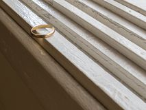 An old gold ring on a white furniture. Only an old wedding ring, in gold, on a white dresser Stock Photos