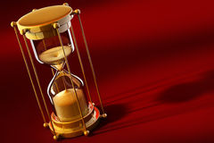 Old gold sand clock measuring time. On the red background - 3d illustration Stock Images