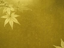 Old gold wall with maple leaves Royalty Free Stock Image