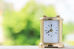 An old golden alarm clock with nature background. An old golden alarm clock on wooden board with nature background Royalty Free Stock Photo