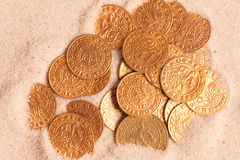 Old golden coins in sand Stock Image