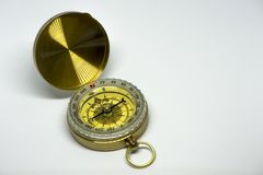 An old golden compass on a white background stock photography