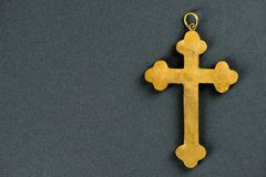 Old golden cross against grey background. Old golden christian cross without chain against grey background Stock Images