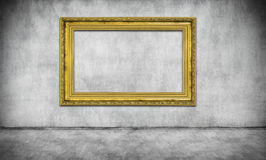 Old golden frame on gray wall. Old golden empty frame on gray wall Royalty Free Stock Photo