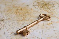 Old golden key on map stock images