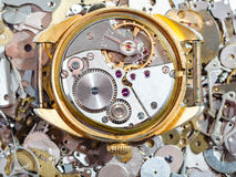Old golden watch on heap of clock spare parts. Watchmaker workshop - open old golden mechanical wristwatch on heap of clock spare parts Stock Photos