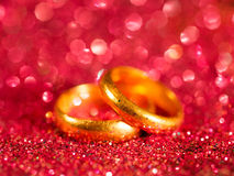 Old golden wedding rings on blurred red sparkle background Royalty Free Stock Photo