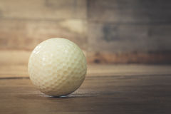 Old golf ball. On wooden Royalty Free Stock Photos