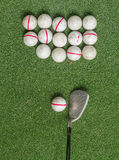 Old golf balls and iron on artificial grass in driving range. Stock Images