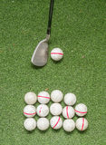 Old golf balls and iron on artificial grass. Royalty Free Stock Photos