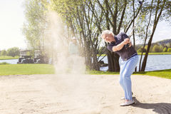 Old golf player pitching from bunker. Senior golfer swinging golf club in sand bunker Royalty Free Stock Image