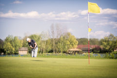 Old golf player pitching onto green. royalty free stock photography
