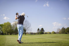 Old golfer shooting on green. Male senior golf player hitting ball on fairway Royalty Free Stock Photos