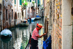 An old gondolier moors his boat in a canal in Venice. VENICE, ITALY - JUNE 4, 2016 - An old gondolier moors his boat in a canal in Venice stock image