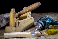 Old good carpentry, tools drill bit. Wooden carpentry table and. Old good carpentry tools on it. Black background Stock Image