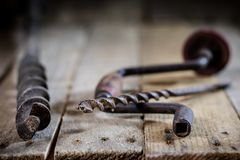 Old good carpentry, tools drill bit. Wooden carpentry table and. Old good carpentry tools on it. Black background Royalty Free Stock Images