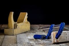Old good carpentry, tools drill bit. Wooden carpentry table and. Old good carpentry tools on it. Black background Stock Photo