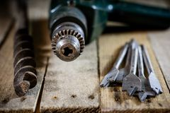 Old good carpentry, tools drill bit. Wooden carpentry table and. Old good carpentry tools on it. Black background Royalty Free Stock Image