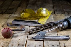Old good carpentry, tools drill bit. Wooden carpentry table and. Old good carpentry tools on it. Black background Royalty Free Stock Photography