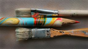 Old good tools of a creative person or painter. Brushes made of pig bristles and a huge color pencil Stock Photos