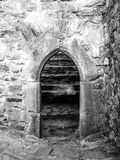 Old gothic arc gate in medieval stone castle ruin. Black and white image Royalty Free Stock Photos