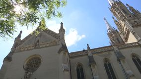 Old Gothic cathedral on a summer day with blue sky. Pan shot stock video