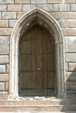 Old gothic door in a thick stone wall. Old gothic door in a thick yelow stone wall Royalty Free Stock Photography