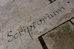 Letters on a stone wall. Old gothic stone wall with latin word scriptorium which means a room for copying manuscripts Stock Photo
