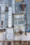 Old grain elevator. Industrial background - a metal exterior of old grain elevator with pipes, ducts, ladders and chutes Royalty Free Stock Photography