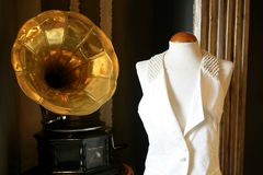 Old gramophone. Old brass golden gramophone and fashion costume in mennequin stock image