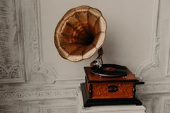 Old gramophone with horn speaker stands against anicent background, produces songs recorded on plate. Music and nostalgia concept. Gramophone with phonograph royalty free stock images