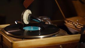 Vinyl plate is spinning on an old pathephone , finishing record. Old gramophone is playing a black shellac record. A rare vintage phonograph records are saved stock footage