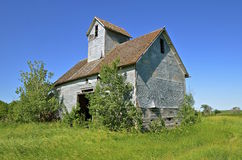 Old granary surrounded by bushes Royalty Free Stock Photography