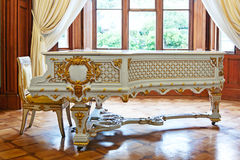 Old grand piano. Old white grand piano decorated with gold in palace room stock photos