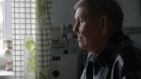 Old grandfather looking thoughtfully aside sits stock video