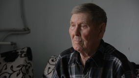 Old grandfather looking thoughtfully aside sits stock video footage