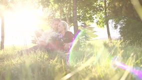 Old grandma and grandpa sitting in park on grass. stock video