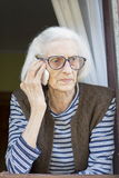 Old grandma talking on the phone standing on her window Royalty Free Stock Photos