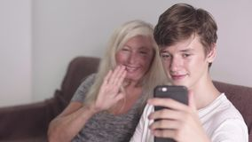 Old grandmother and adult grandson using mobile application on phone tougether seating on the sofa. Doing video call stock video footage