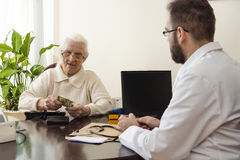 The old grandmother deducts the money in the doctor`s office. Private medical practice. Grandma pays the doctor for a visit to a private doctor`s office Royalty Free Stock Photo