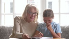 Old grandmother helping granddaughter school child girl with homework. Old grandmother or senior teacher tutor helping granddaughter school child girl doing stock video