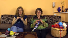 Old grandmother knit with nurse woman on sofa in nursing home stock video footage