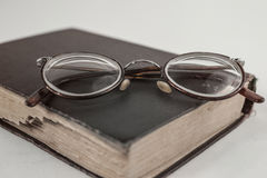 Old grandmother`s glasses and a dilapidated book Royalty Free Stock Photography