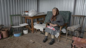 Old grandmother sitting in an armchair outdoors smiling stock video