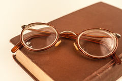 Old grandmother& x27;s glasses and a dilapidated book Royalty Free Stock Photography