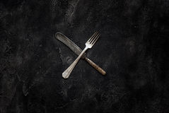Old grange knife and fork X on concrete top view Stock Photo