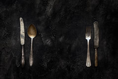 Old grange knife, spoon and fork on concrete top view Stock Photos