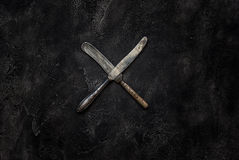 Old grange knifes X on concrete top view Stock Photo