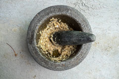 Old granite mortar with pestle and garlic Royalty Free Stock Images