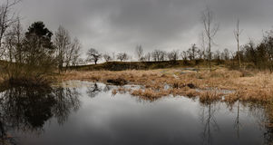 Old granite quarry with lake before storm panorama Royalty Free Stock Image